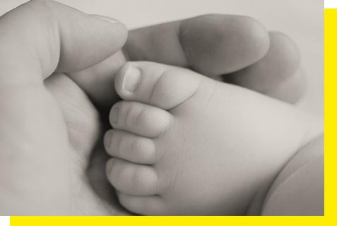 Pied de bébé dans la main d'un ostéopathe