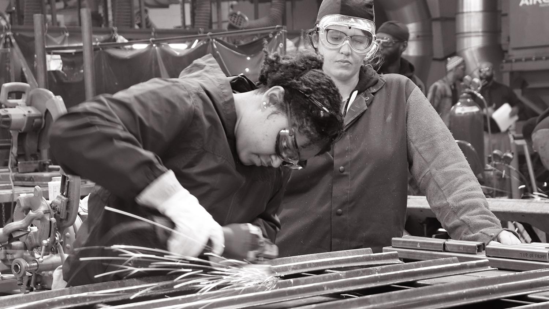 zwei Frauen in Arbeits- und Schutzkleidung, die eine schweisst, die andere schaut zu
