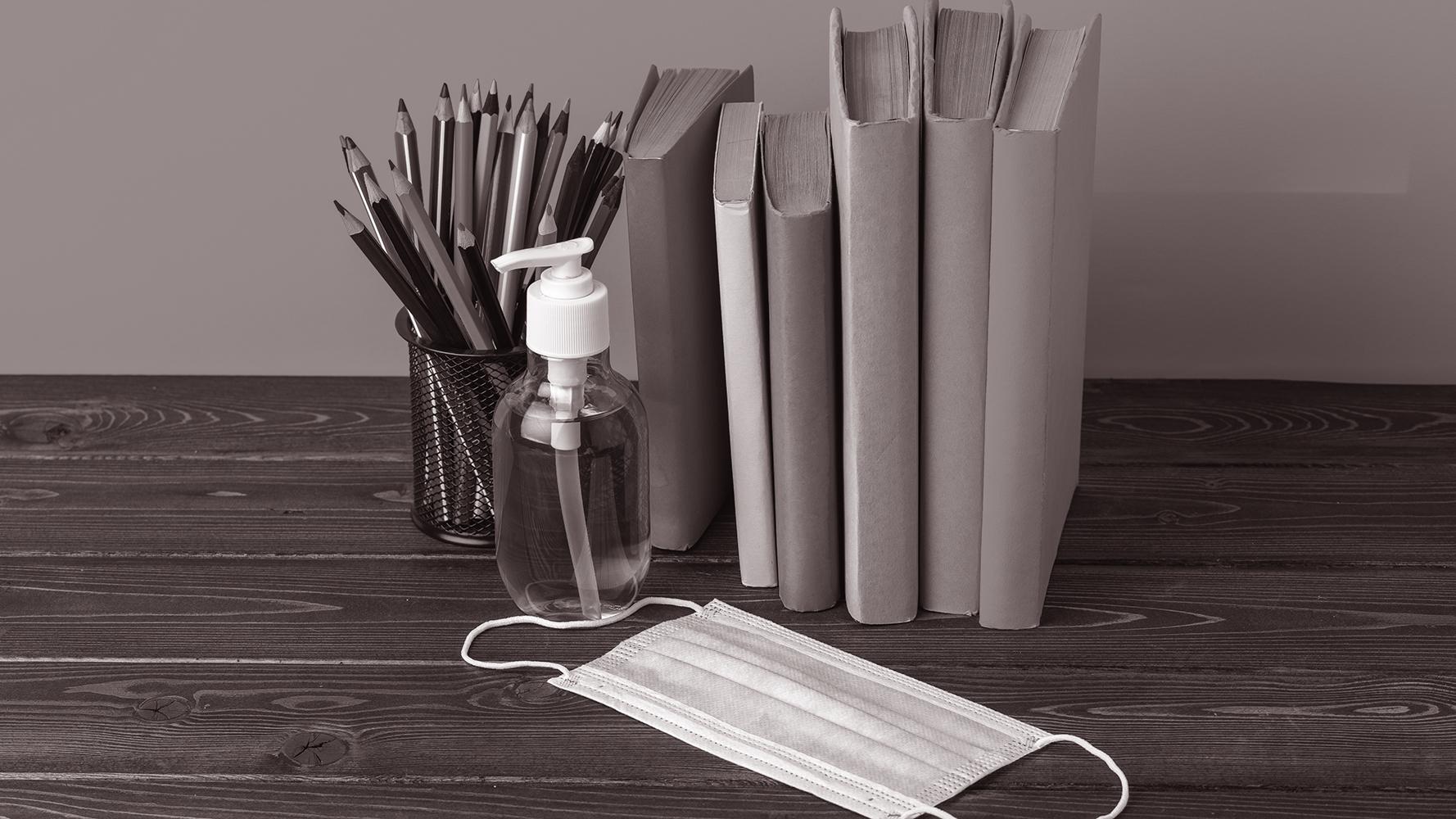 Stifte, Bücher, Desinfektionsmittel, Maske liegen auf einem Holztisch