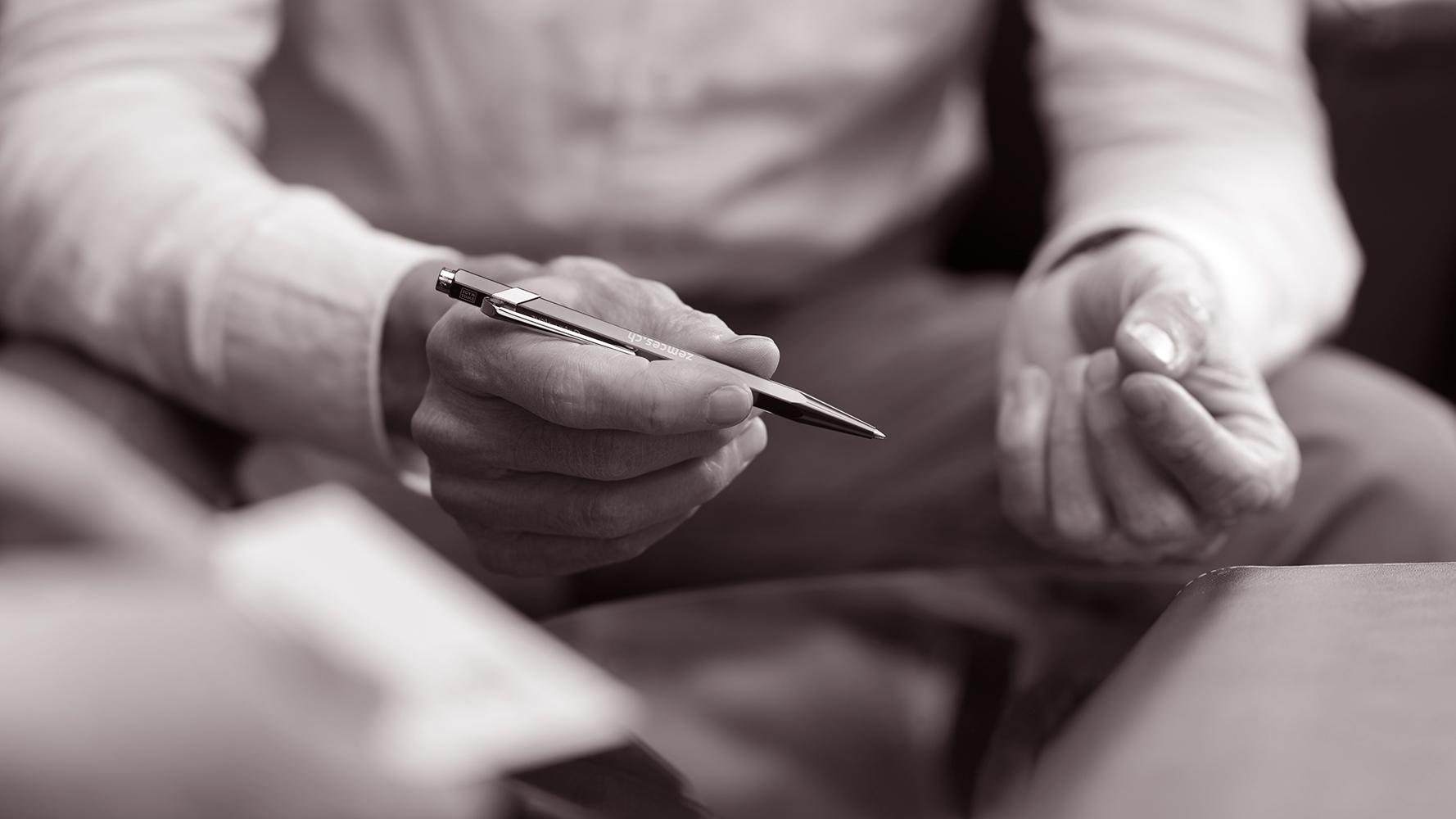 Zwei Hände, die rechte Hand hält einen Stift