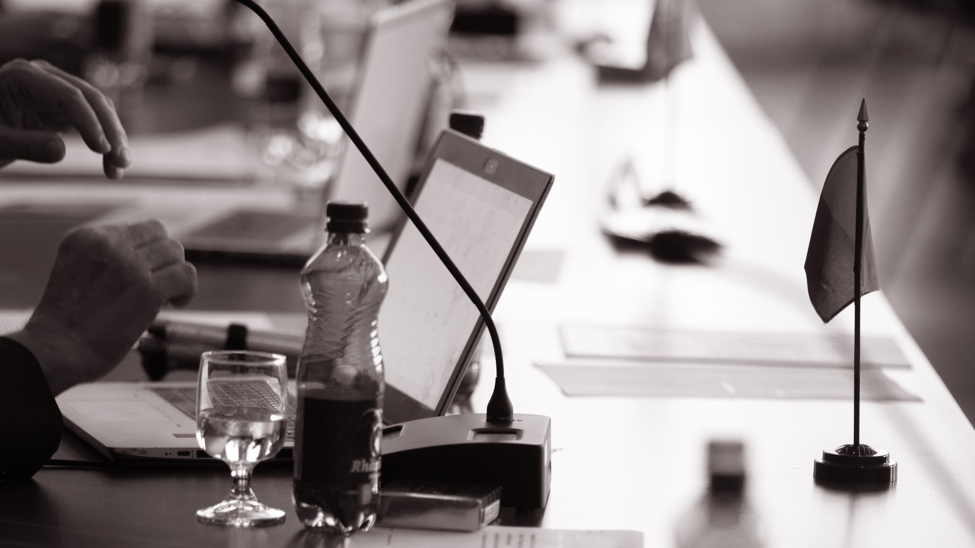 Detailsicht Tisch während Plenarversammlung; Laptop, Mikrofon, Wasserflasche und -glas, Wimpel